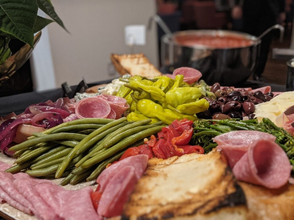 deli tray with meat, bread, peppers, green beans, and sauces